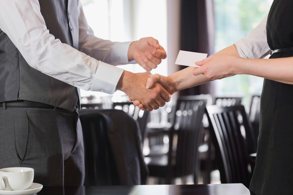 Business people shaking hands after meeting and changing cards in restaurant-1